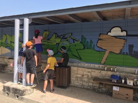 Enfants qui créent leur fresque en graff sous l'abribus